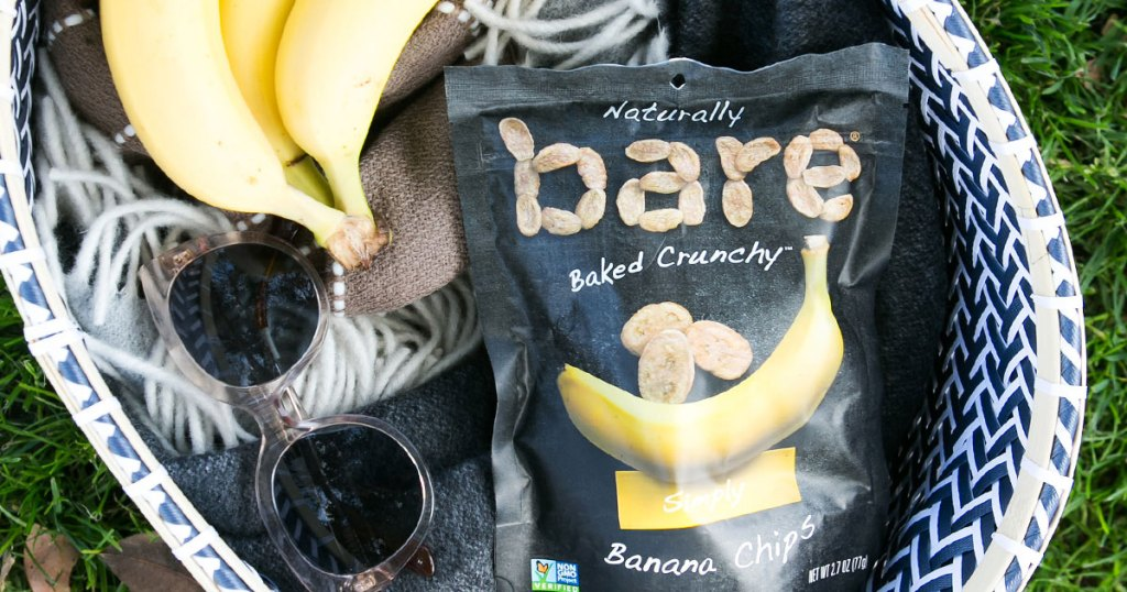 bare baked banana chips bag in basket with bananas and pair of sunglasses