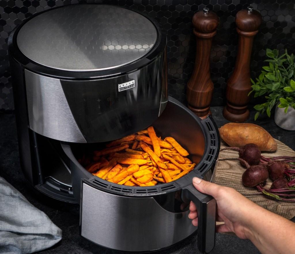 hand opening an air fryer