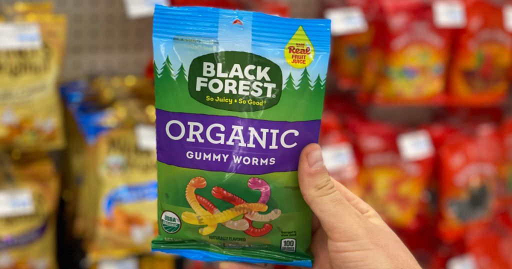Hand holding package og gummie worm candy