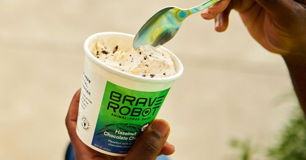 person sticking spoon into pint of brave robot ice cream