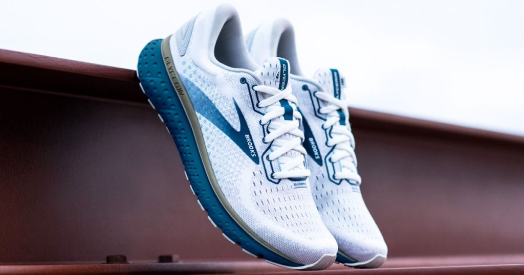 pair of white and blue running shoes leaning against stairs