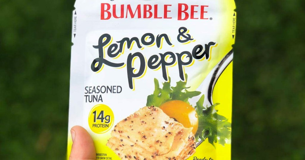 person holding up packet of bumble bee tuna in lemon pepper flavor