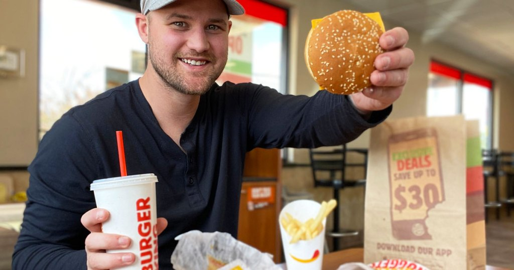 man holding up a burger king burger and drink