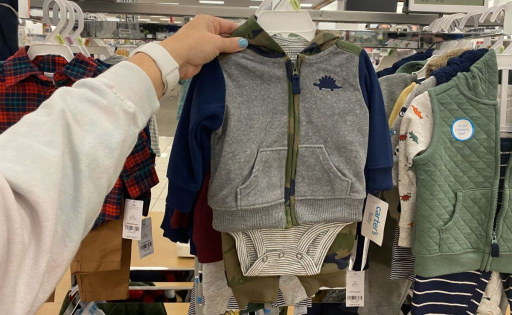 hand holding a Carter's baby outfit