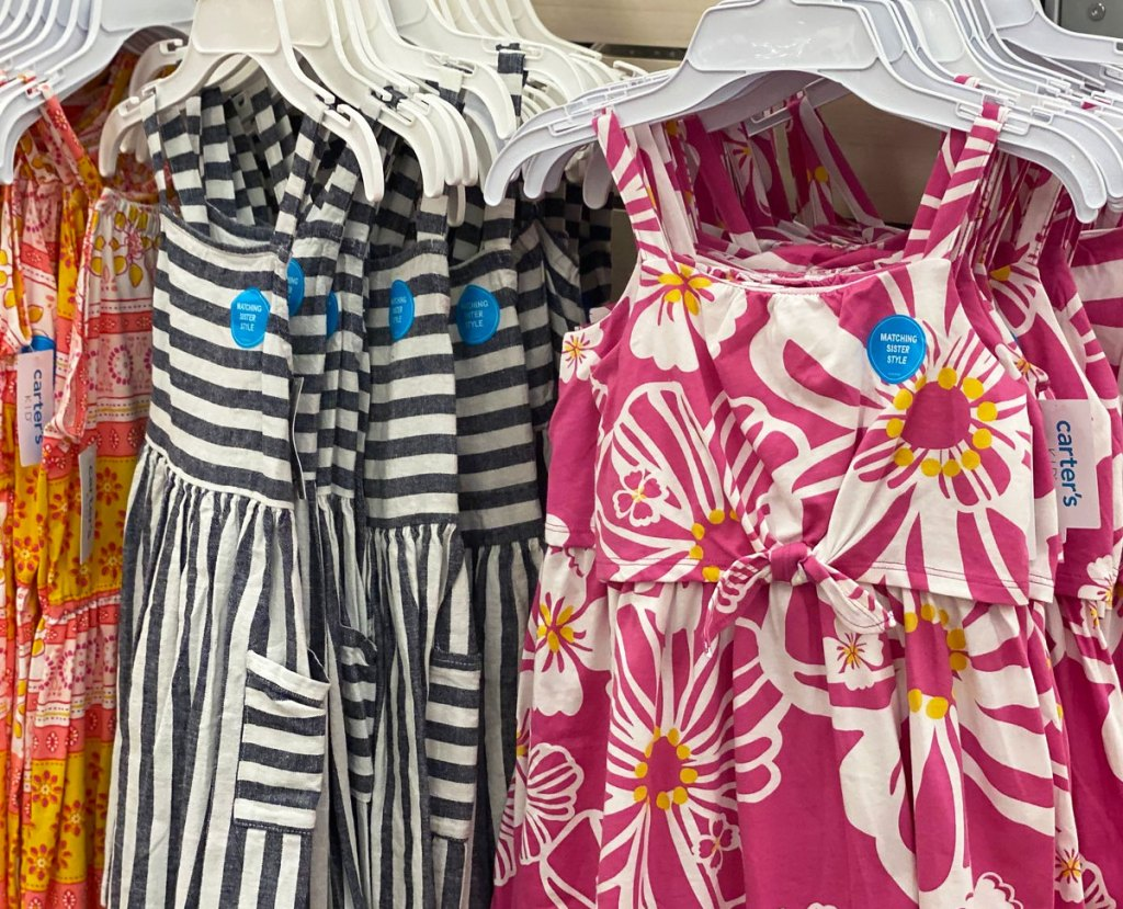 carter's girls dresses on hangers in store