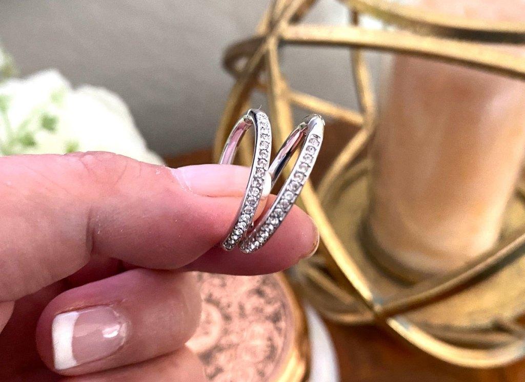 hand holding pair of white gold hoop earrings