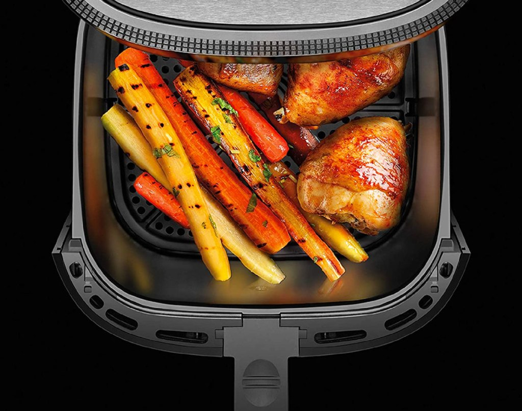 air fryer with basket open with chicken and carrots inside