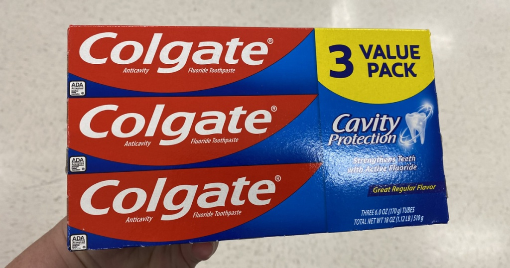 Hand holding up Colgate Toothpaste 3 pack