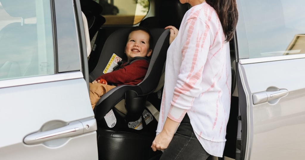 Mom standing near toddler in car seat in van