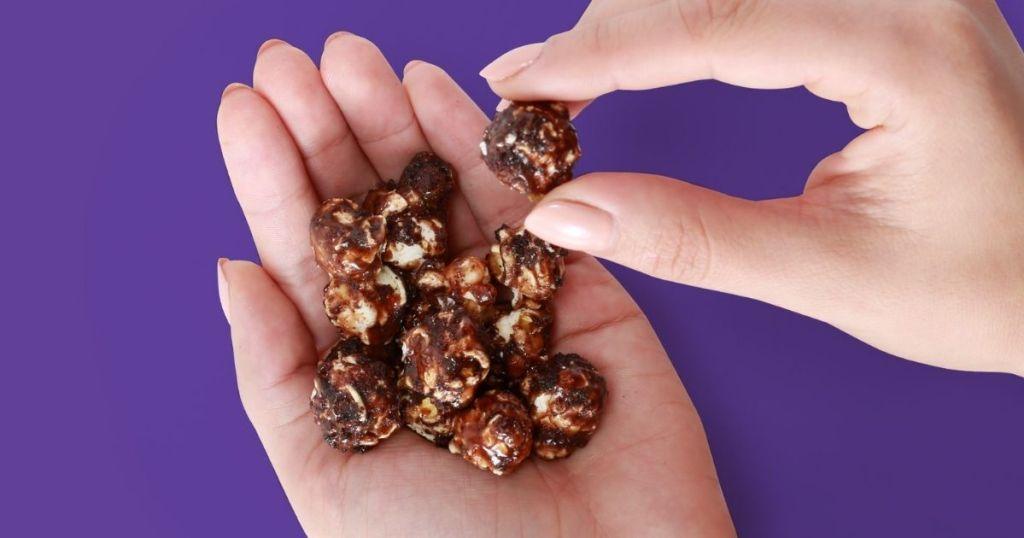 woman's hand holding Crunch 'n Munch Brownie Crunch