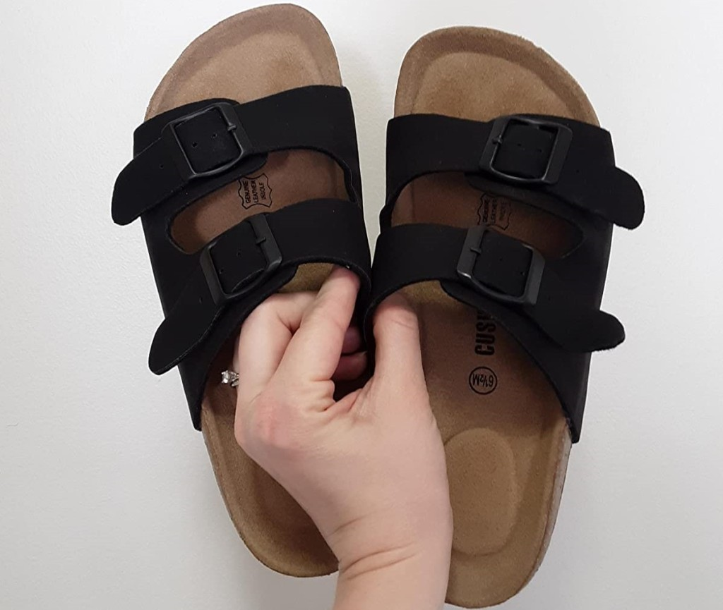hand holding a pair of sandals