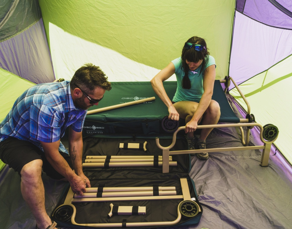 man and woman building a bunk bed cot