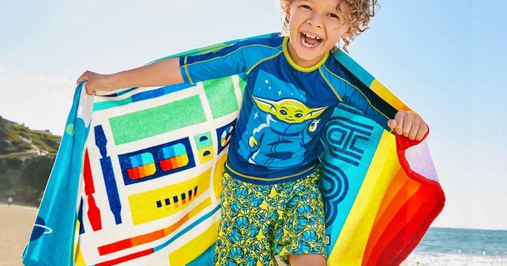 boy in star wars swimwear with colorful beach towel