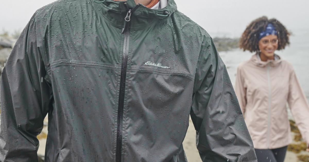man wearing an eddie bauer rain jacket standing in front of a woman wearing a rain jacket