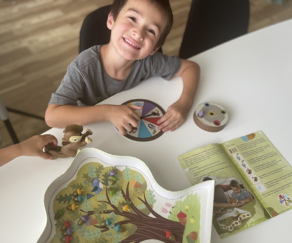 boy smiling and playing squirrel game at table