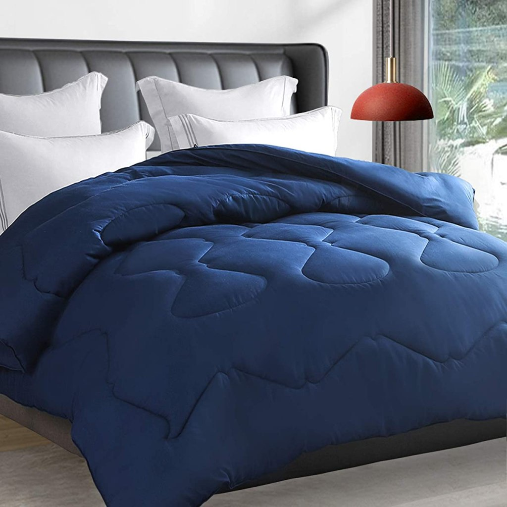 blue comforter on a bed with white pillows