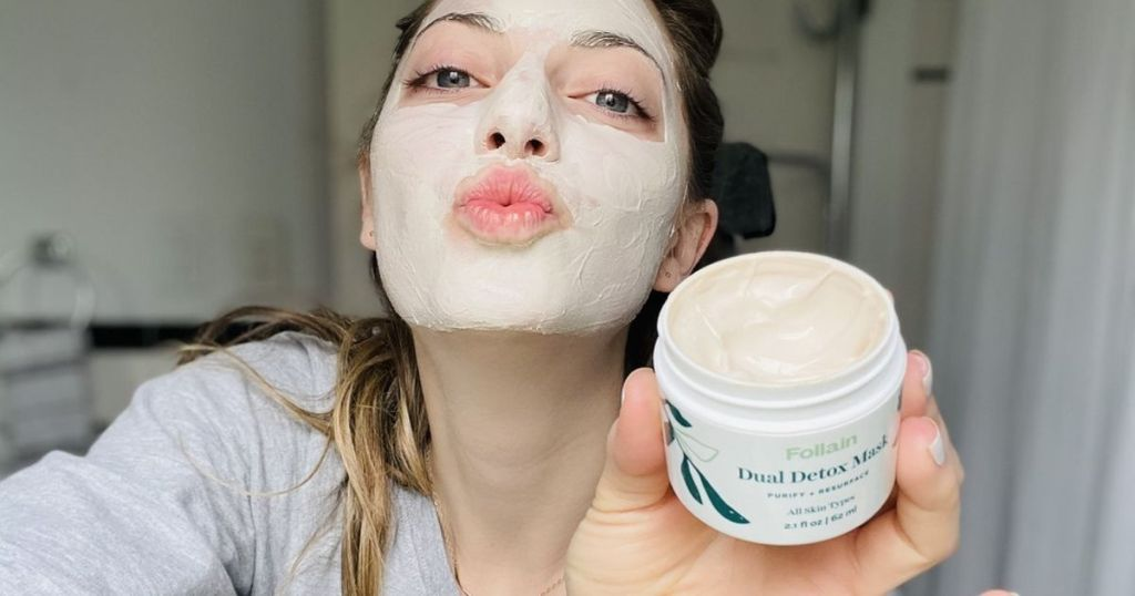 woman with facial mask on her face and holding up container