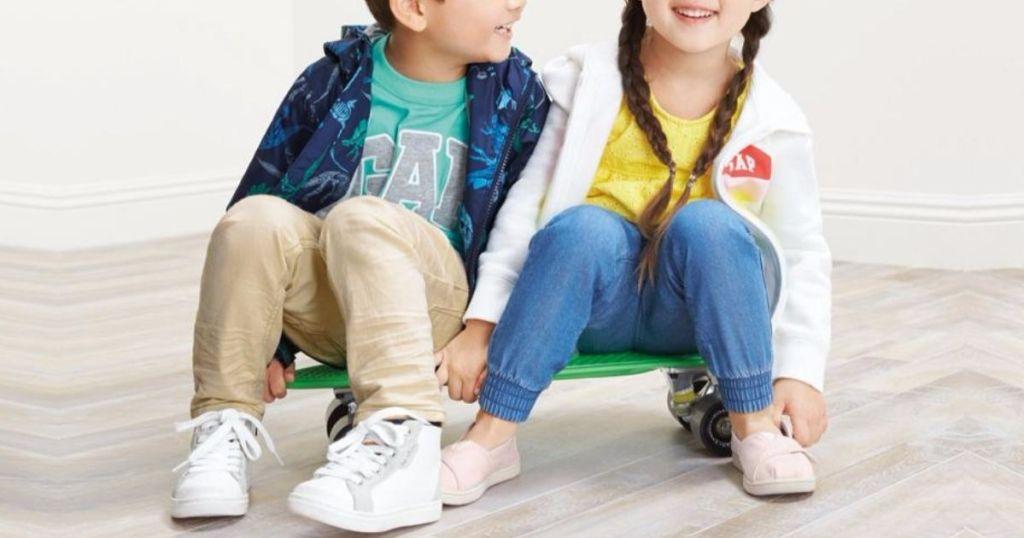 two kids sitting on a skateboard