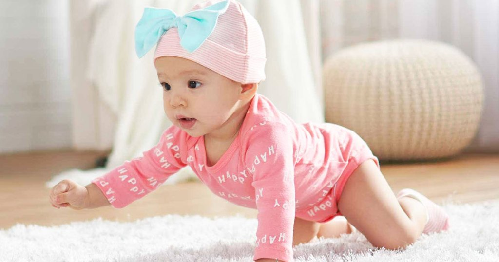 baby girl crawling on floor wearing pink onesie and hat with bow