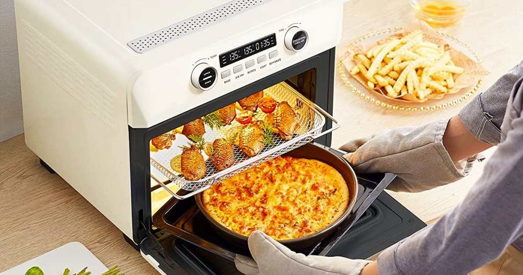person taking food out of a large air fryer oven