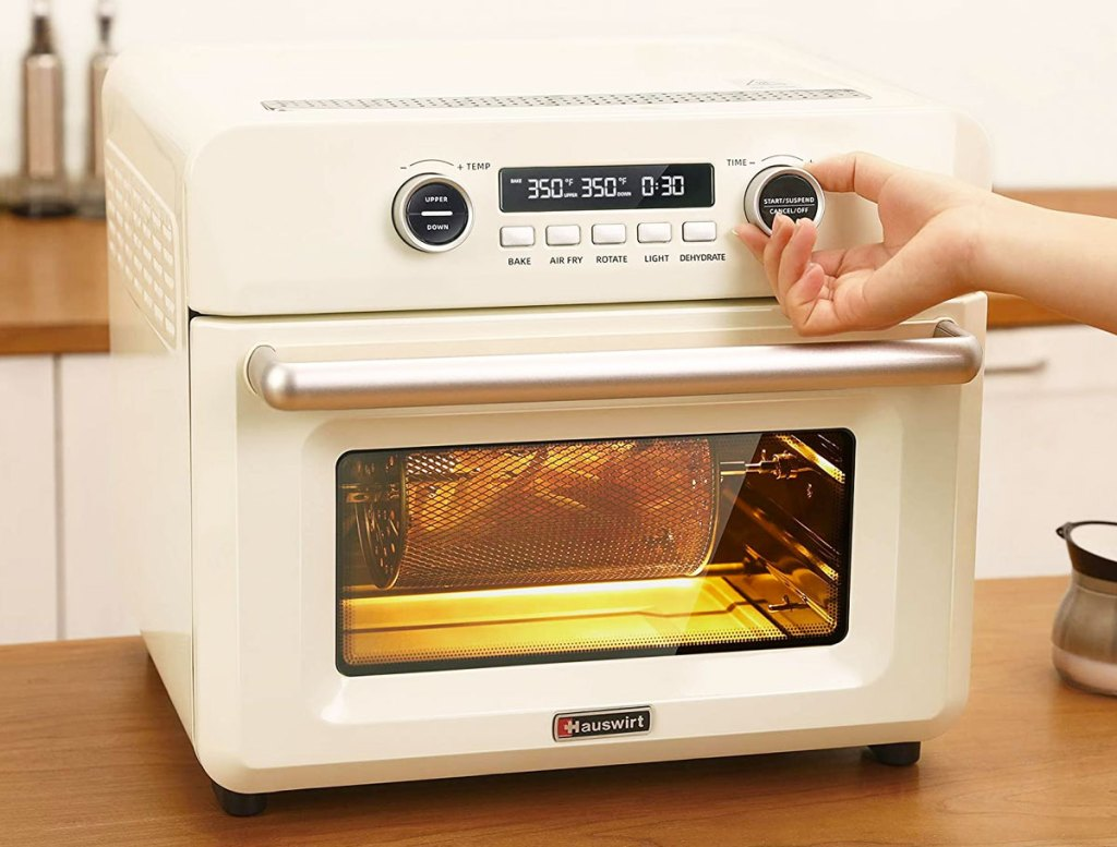 person adjusting temperature on white air fryer oven