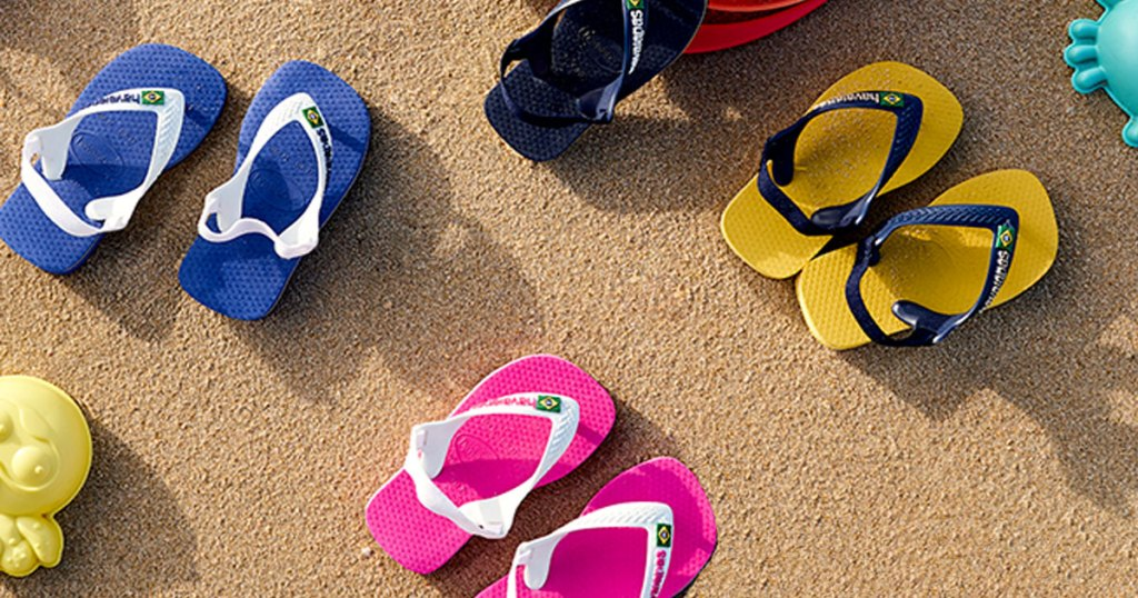 multiple pairs of toddler sandals in sand