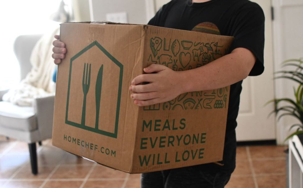person carrying a Home Chef box