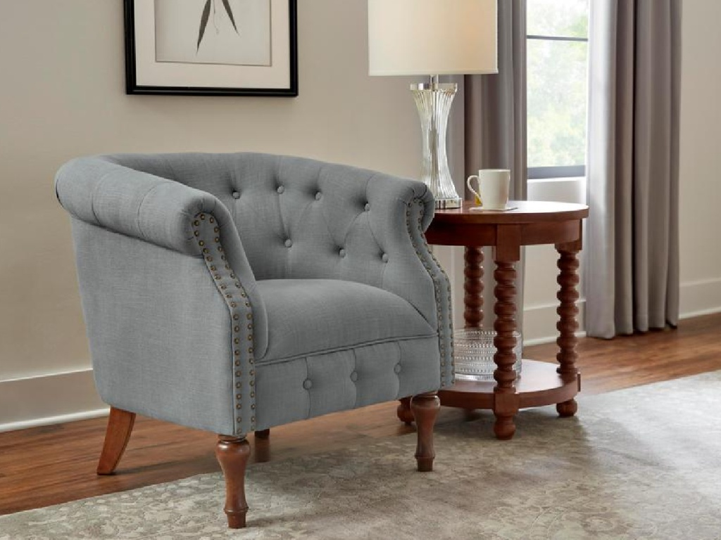 grey tufted chair next to side table and lamp