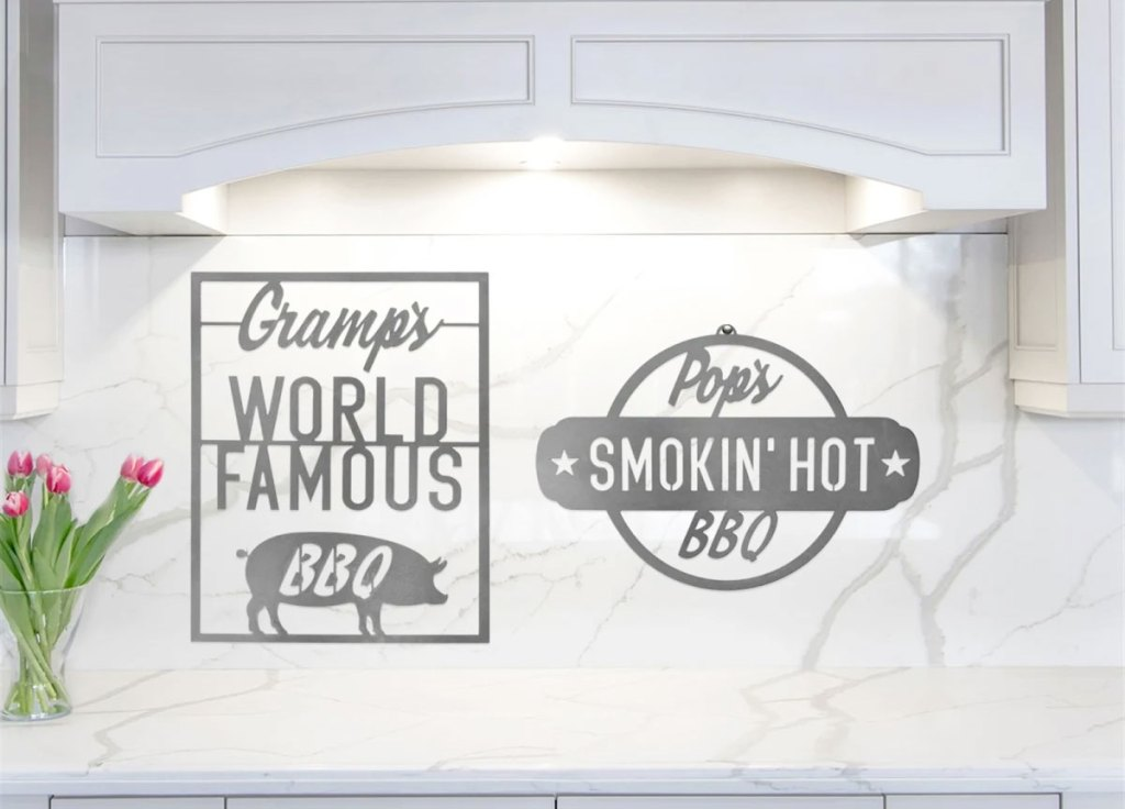 two metal bbq signs on kitchen wall