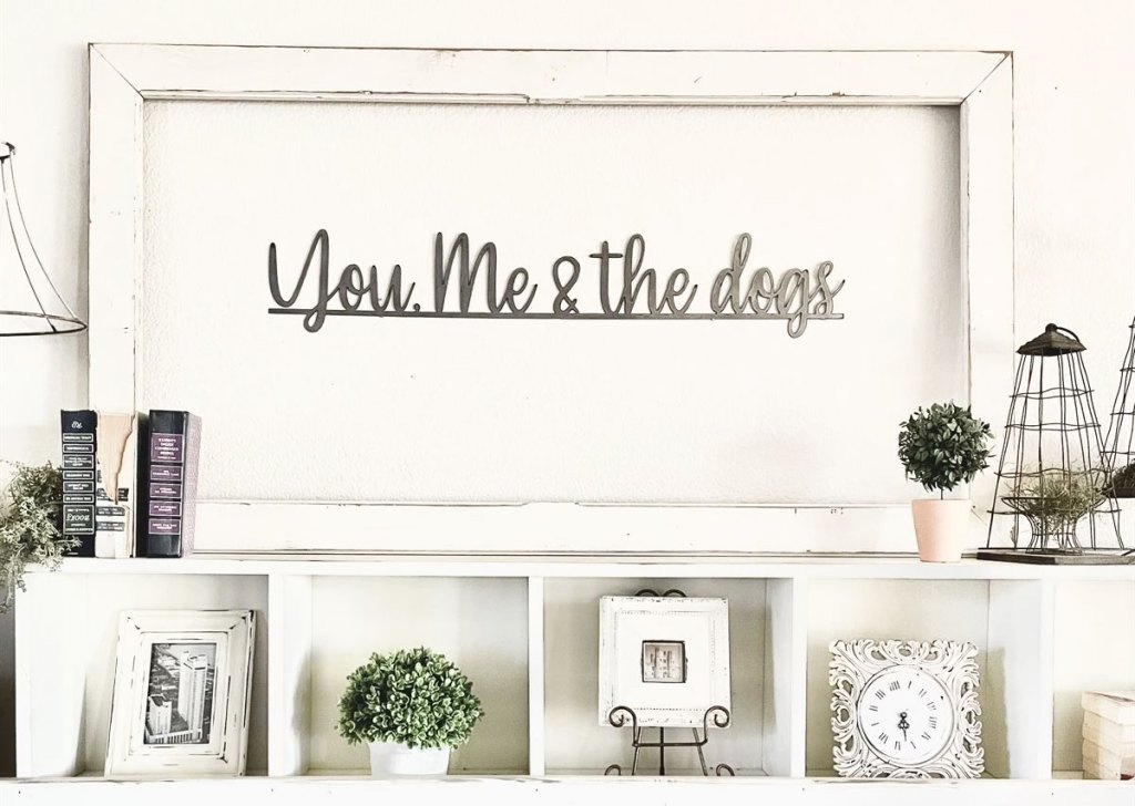metal sign on wall that says you, me & the dogs