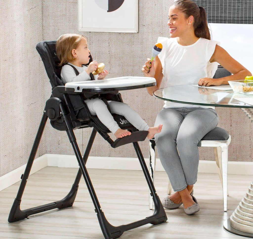 baby in high chair next to woman sitting at table