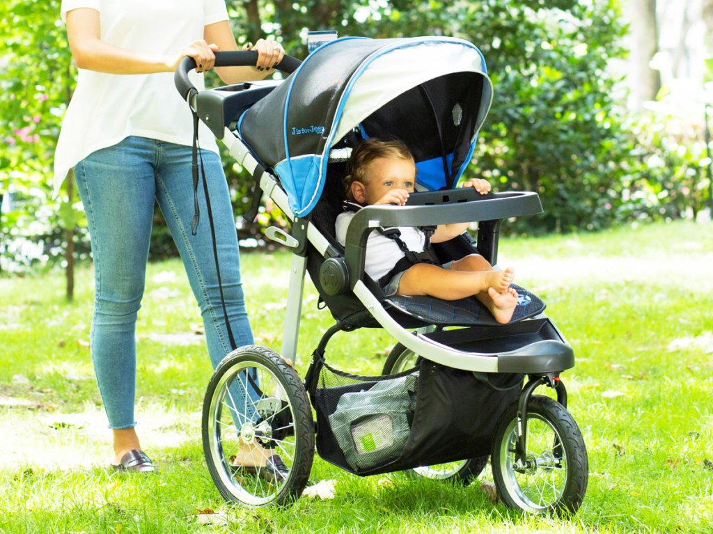 woman pushing child in jogger stroller