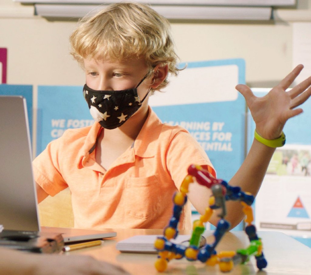 boy wearing face mask in front of laptop