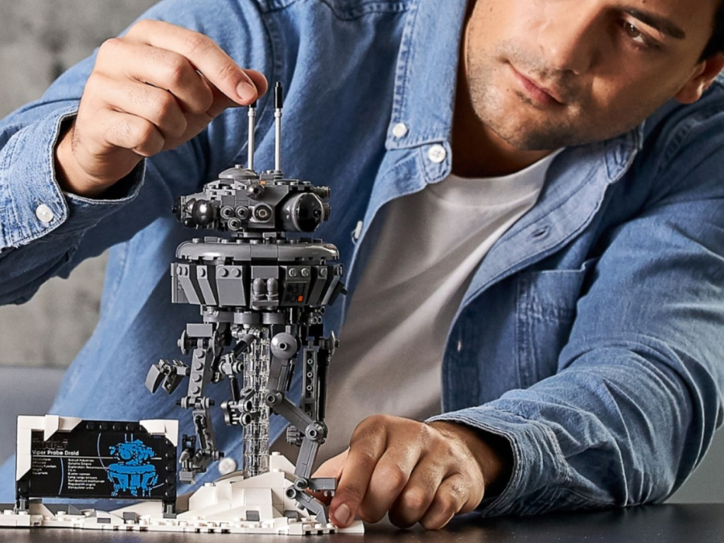 man putting together lego droid