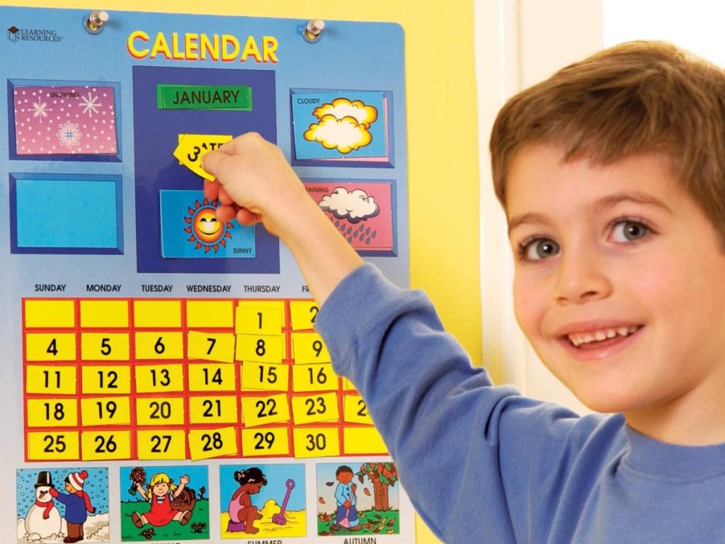 little boy standing next to a wall calendar