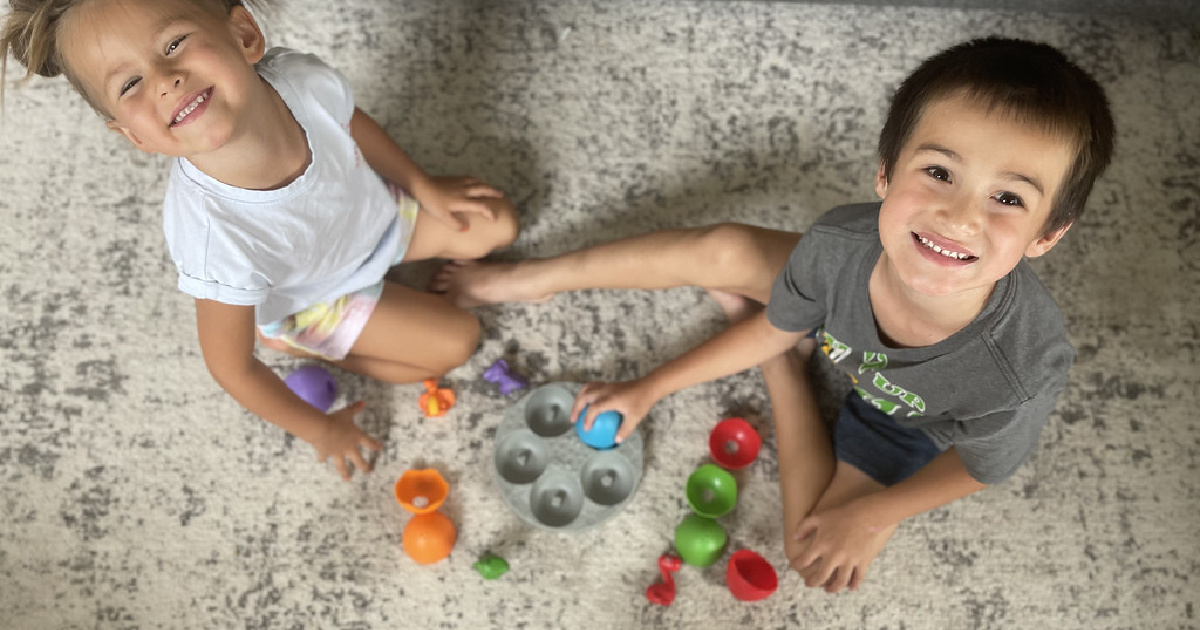 girl and boy playing with a sorting game sitting on a rug looking up at the camera