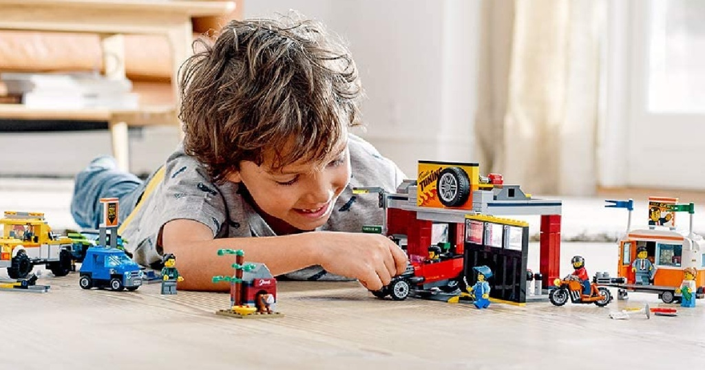boy laying on the floor playing with lego city car tuning set