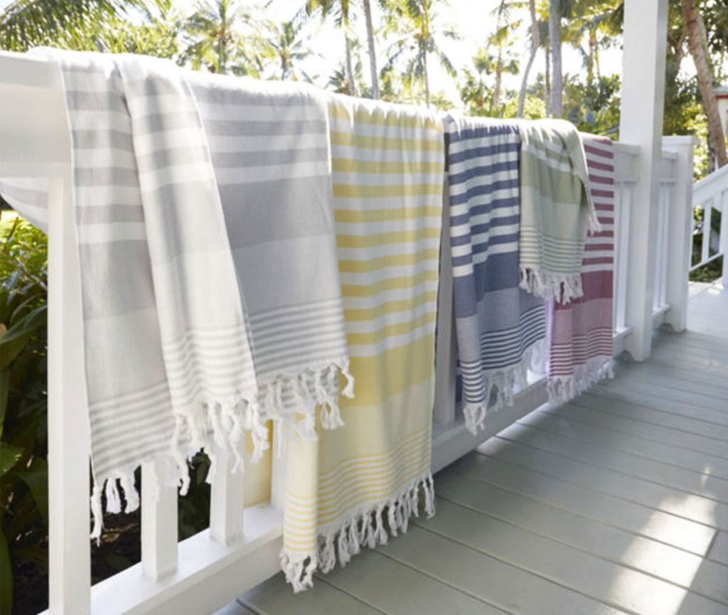 striped beach towels hanging over rail