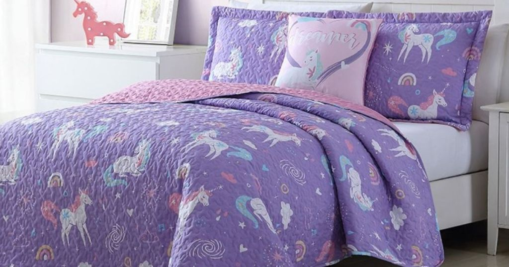 bed with a unicorn quilt on it