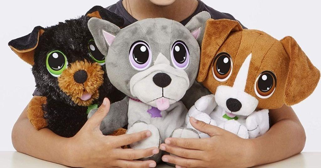 child holding 3 Little Tikes Cuddle Pups