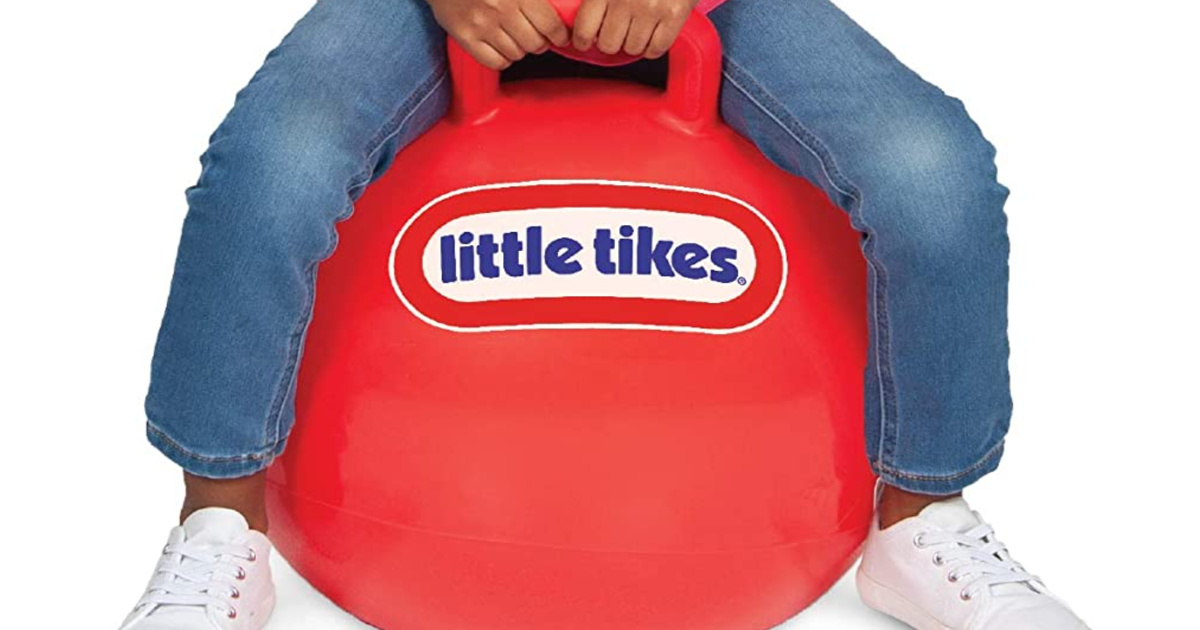 girl wearing jeans sitting on a red hopper ball