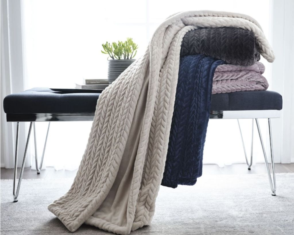 4 Loom + Forge Faux Mink Chevron Throws on a bench in a room
