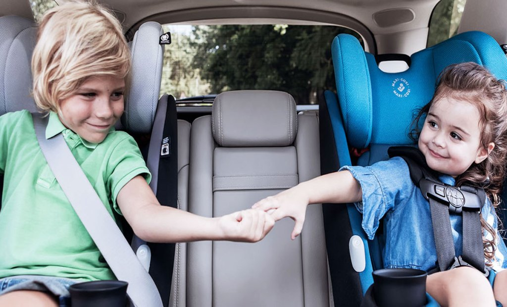 two kids holding hands sitting in car seats in car