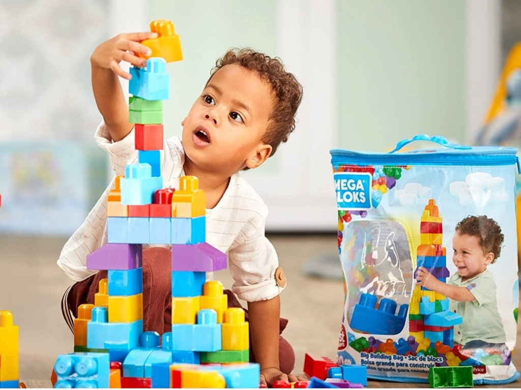 boy playing with large building blocks on floor