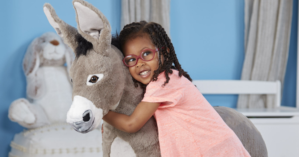 young girl hugging a large gray stuffed donkey