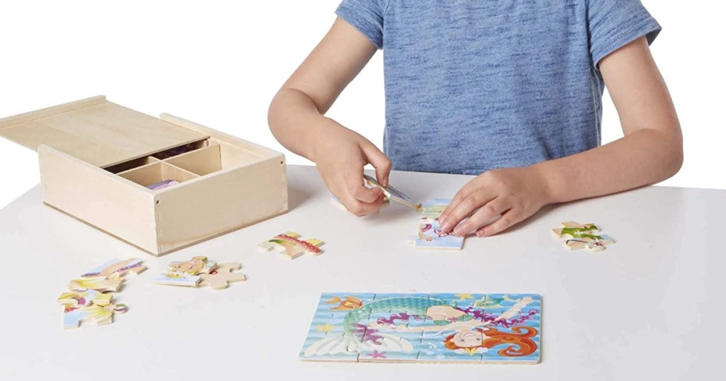 young child playing with a puzzle on a table