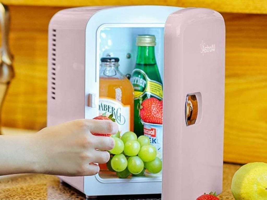 hand getting grapes from pink mini fridge