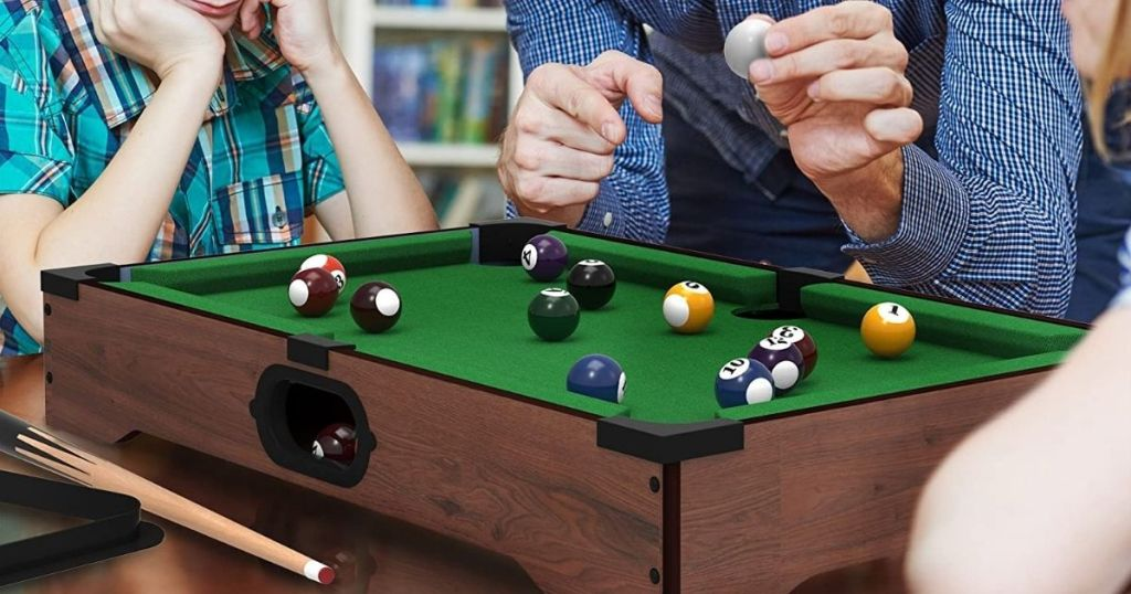 people by a mini pool table