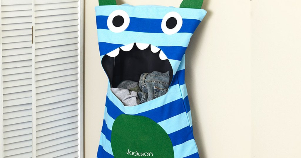 blue striped monster laundry hamper hanging on wall