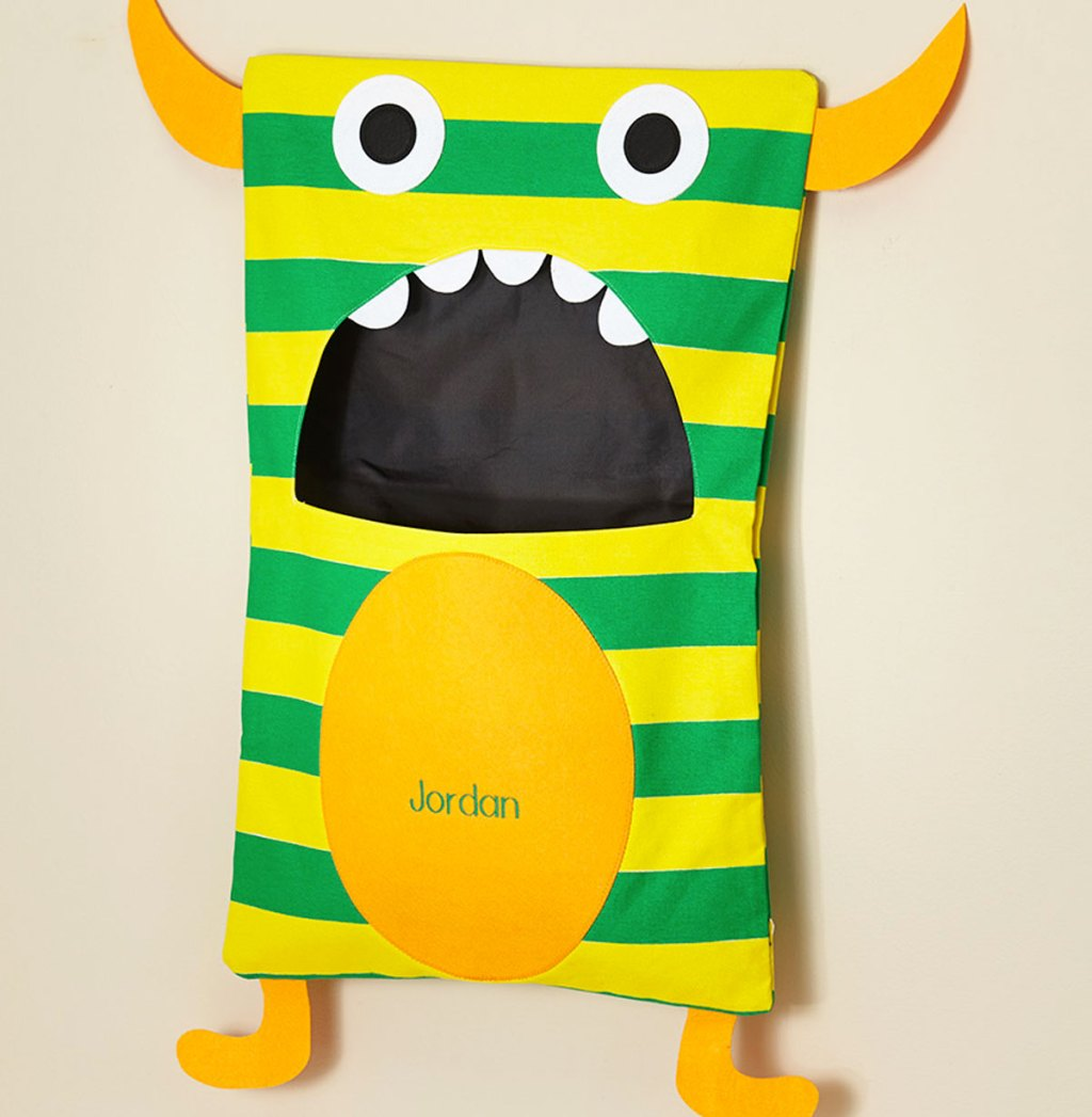 yellow and green striped monster laundry hamper hanging on wall